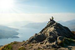 在山顶部的女性远足者享受谷视图的 库存图片