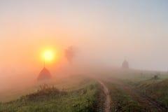在山领域的日出 干草堆和路在有薄雾的秋天 免版税库存图片