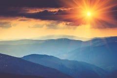 在山风景的五颜六色的日落 严重的阴暗天空 免版税库存照片