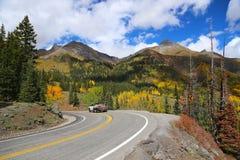 在山高速公路的一辆平板车卡车在秋天峰顶颜色期间的科罗拉多落矶山 免版税图库摄影
