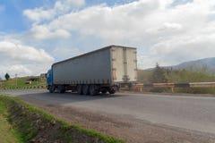 在山高速公路的货物卡车 免版税库存照片