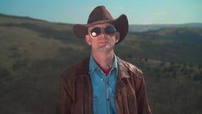 在山,牛仔帽的,皮夹克,玻璃一个人 一个人接触他的帽子用他的手 股票视频