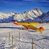 在山滑雪胜地机场的黄色红色飞机瑞士人的 库存图片