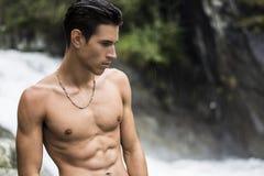 在山waterfa附近的英俊的赤裸上身的年轻人 库存照片