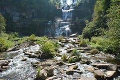 在岩石上的瀑布落下的水在下面小河 免版税图库摄影