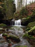 在岩石下的瀑布 免版税库存照片