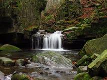 在岩石下的瀑布 图库摄影