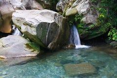 在岩石中的一点瀑布在山森林里 免版税图库摄影
