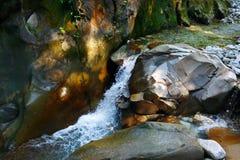 在岩石中的一点精采瀑布在山森林里 库存照片