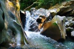 在岩石中的小的光彩的刷新的瀑布 免版税库存照片