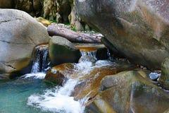 在岩石中的小的奇妙刷新的瀑布 库存照片