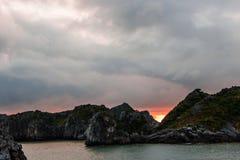 在岩石中的明亮的日落在下龙湾 库存图片