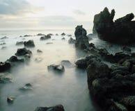 在岩石中的雾在海岸线 库存照片