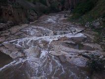 在岩石之间的美丽的自然瀑布 免版税库存图片