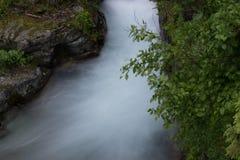 在岩石之间的瀑布在冰川国家公园 免版税图库摄影