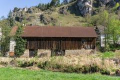 在岩石前面的木谷仓 图库摄影