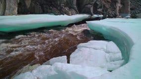 在岩石包围的流动的河的熔化的冰 股票视频