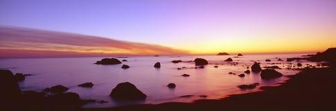 在岩石和平的海岸线的日落 库存图片