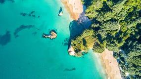 在岩石和森林围拢的一个小海滩的鸟瞰图Coromandel,新西兰 库存图片