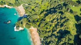 在岩石和森林围拢的一个小海滩的鸟瞰图Coromandel,新西兰 库存照片
