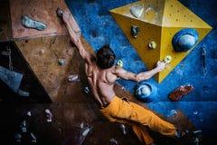 在岩石墙壁上的人实践的攀岩 库存照片