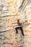 在岩石墙壁上的妇女 免版税库存图片