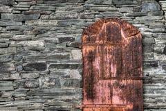 在岩石墙壁上的生锈的老门 库存照片