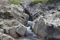 在岩石墙壁之间的小河 图库摄影