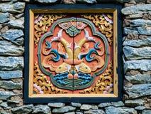 在岩石墙壁的不丹传统木装饰 免版税库存图片