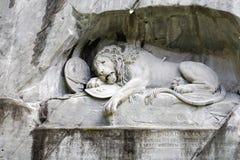 在岩石墙壁雕刻的死的狮子 免版税库存图片