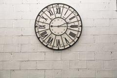 在岩石墙纸背景的一个壁钟 免版税图库摄影