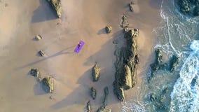 在岩石妇女形象的波浪卷在海滩鸟瞰图 影视素材