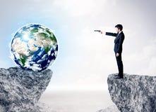 在岩石山的商人与地球 免版税库存照片