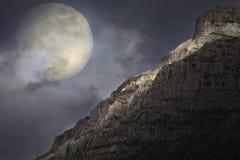 在岩石山顶的上升的满月 免版税库存照片