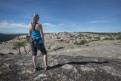 在岩石山顶部的妇女徒步旅行者 库存图片