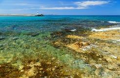 在岩石岸的波浪断裂 海岸和海滩胜地村庄 海上的晴天 库存图片