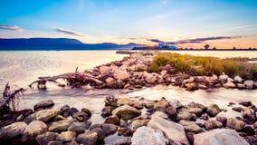 在岩石岸的美好的夏天日落由海 库存照片