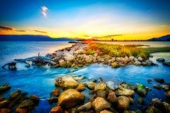 在岩石岸的美好的夏天日落由海 免版税库存图片