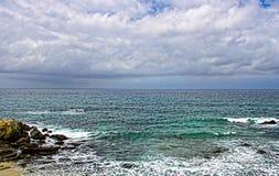 在岩石岸附近的镇静,绿色和蓝色海洋 免版税库存图片