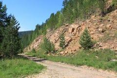 在岩石峭壁附近的农村路 免版税图库摄影