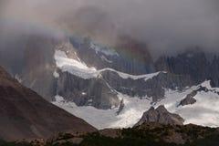 在岩石峰顶和冰川背景的彩虹  库存照片