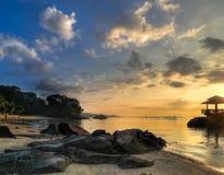 在岩石日出的海滩 库存照片