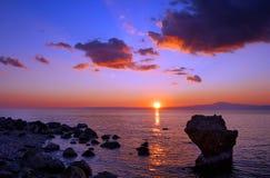 在岩石日落的海滩 免版税库存照片
