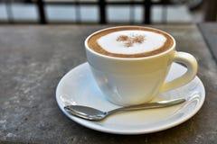 在岩石桌上的热的咖啡杯 库存照片
