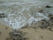 在岩石沙子的波浪 免版税库存照片