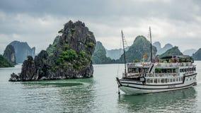 在岩石海岛附近的巡航小船在下龙湾,越南,东南亚 免版税库存照片