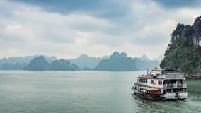 在岩石海岛附近的巡航小船在下龙湾,越南,东南亚 库存照片