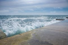 在岩石海岸和蓝色海的大波浪 库存照片