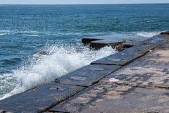 在岩石海岸和蓝色海的大波浪 库存图片
