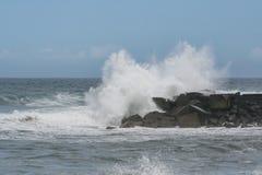 在岩石海岸的碰撞的波浪 免版税库存照片